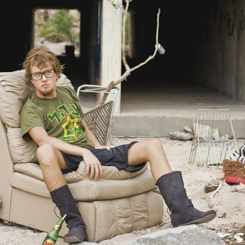 young man with glasses on leather sofa chair outside in dirt
