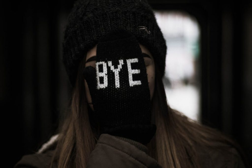 """young woman holding glove over face with word """"bye"""" stitched on it"""
