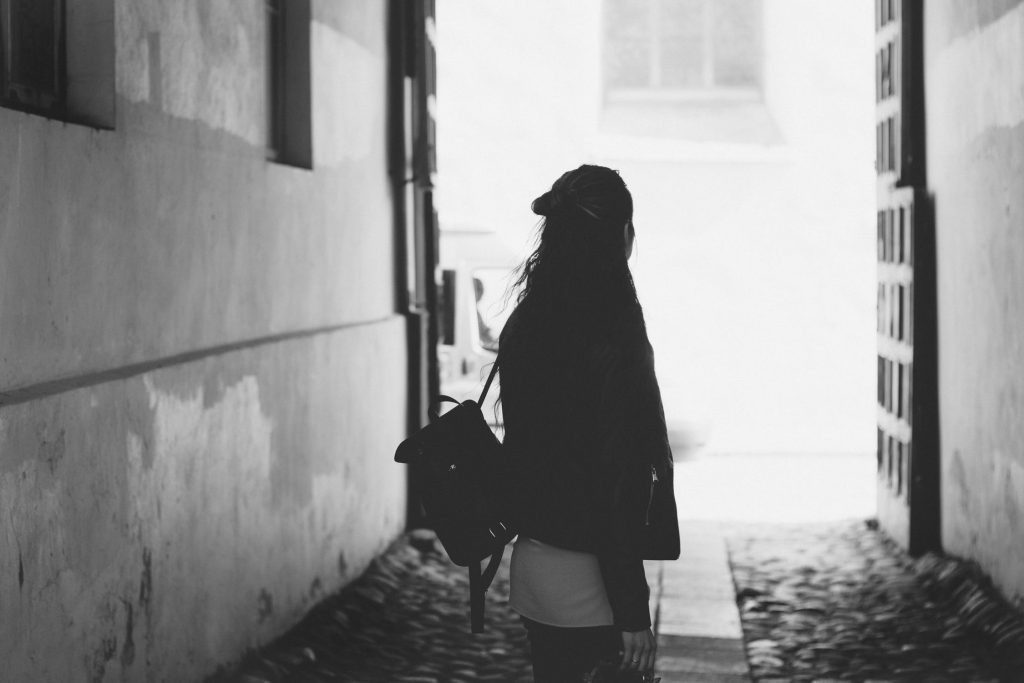 woman with backpack alone in alleyway black and white