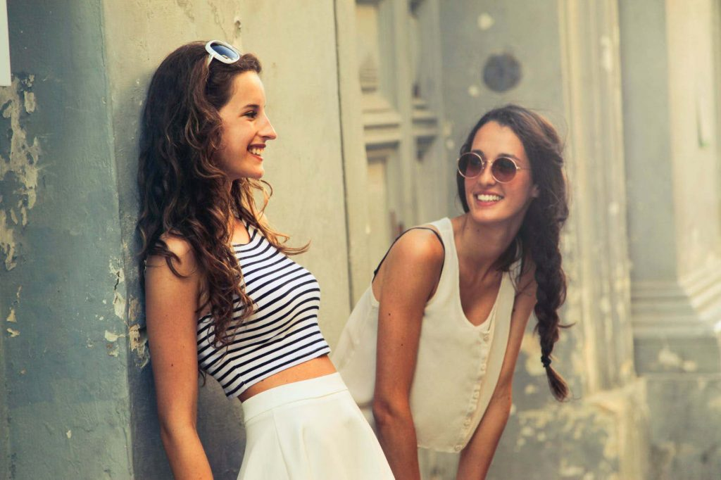 two young women laughing outside building