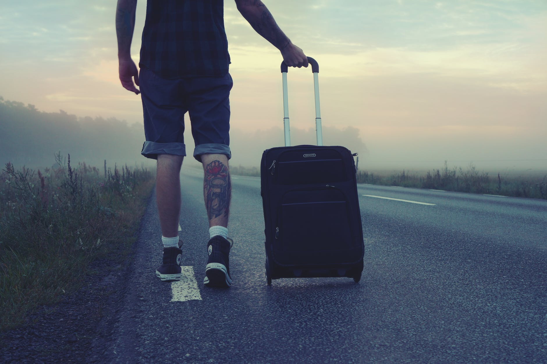 man with leg tattoo rolling suitcase down a long road