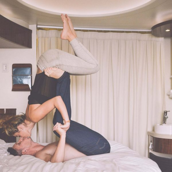 couple in bed kissing and doing AcroYoga