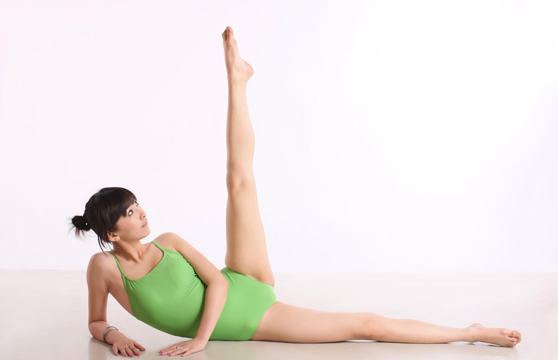 woman in green leotard doing a leg lift