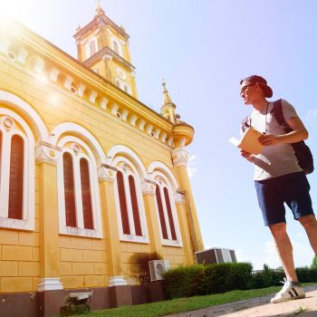backpacker with book outside historic building