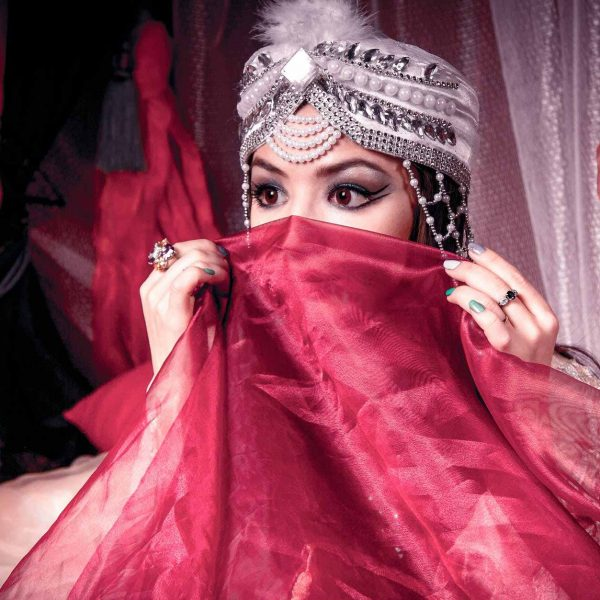elaborately adorned woman covering face with veil