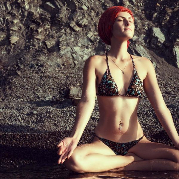 young woman meditating in a swimsuit